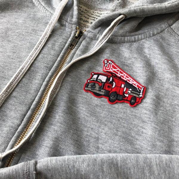 Broderad röd brandbil på grå tröja