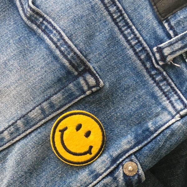 Tygmärke leende Emoji på blå jeans