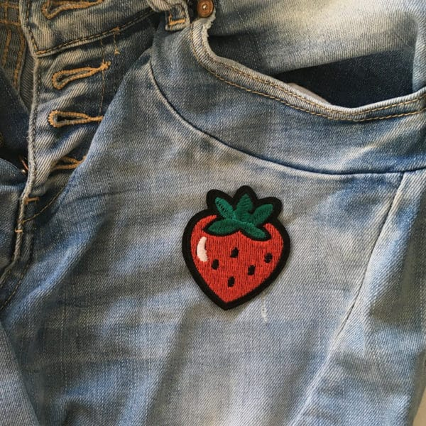 Röd jordgubbe med svarta frön påstrukna på jeans