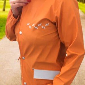 Påstrykbara och självhäftande reflexer på orange regnjacka