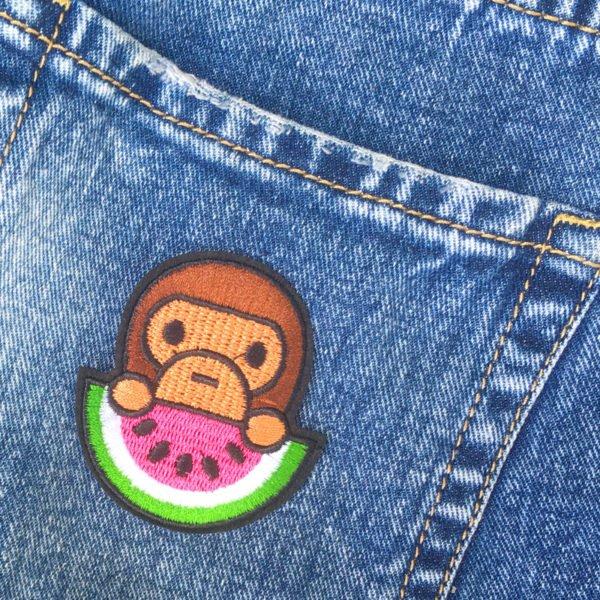Söt apa äter vattenmelon - tygmärke