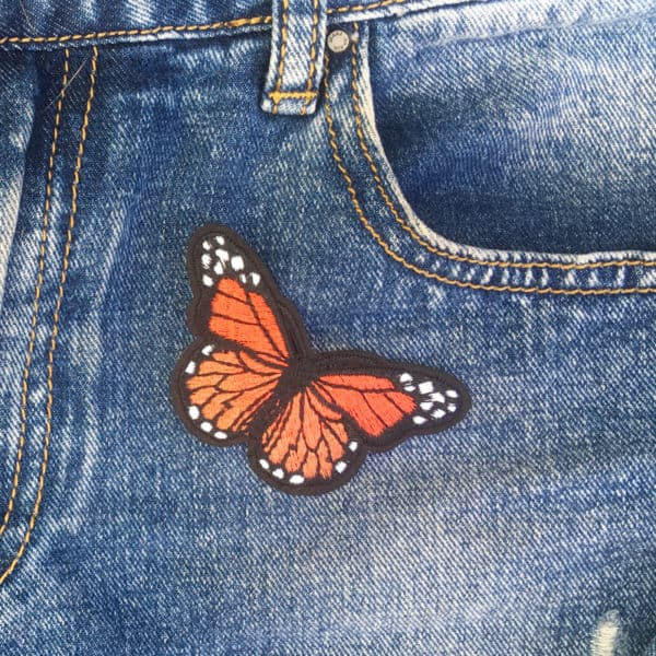 Fjäril eldgul jeans - tygmärke