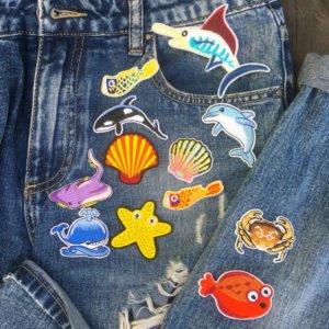 Tygmärken placerade på jeans föreställande havsdjur
