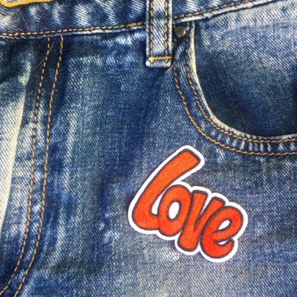 Textmotiv Love röd exempel på jeans - Tygmärke