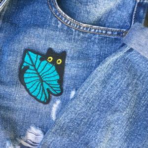Mystisk katt bakom löv jeans - tygmärke
