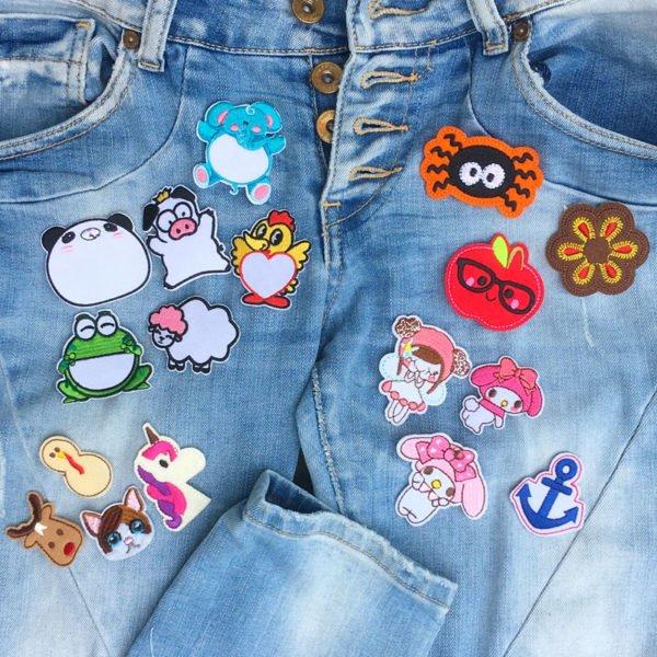 Samling tygmärken med barnmotiv liggandes på jeans