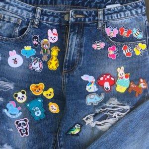 Flera tygmärken placerade på jeans föreställande gulliga djurmotiv