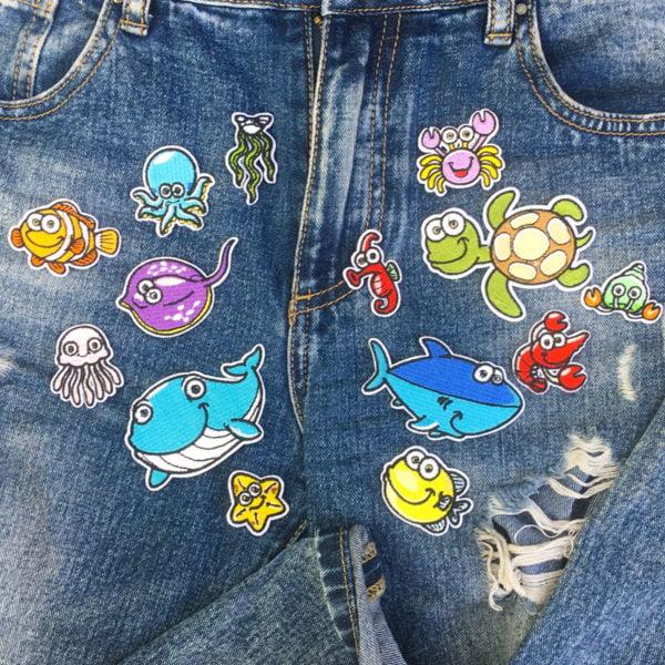 Tygmärken på jeans föreställande valar, fiskar och andra vattendjur