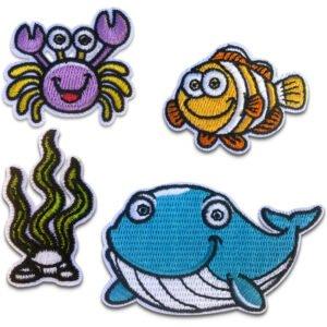 Fyra broderade tygmärken föreställande en val, en krabba, sjögräs och en fisk
