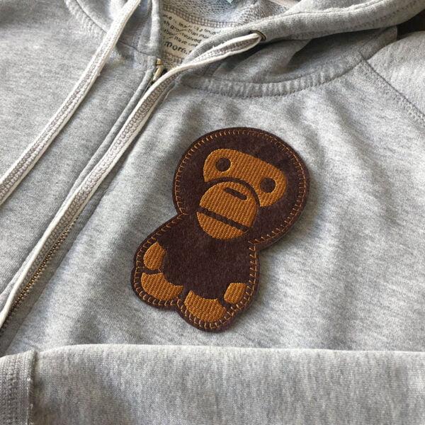 Söt schimpans - broderat tygmärke på grå tröja