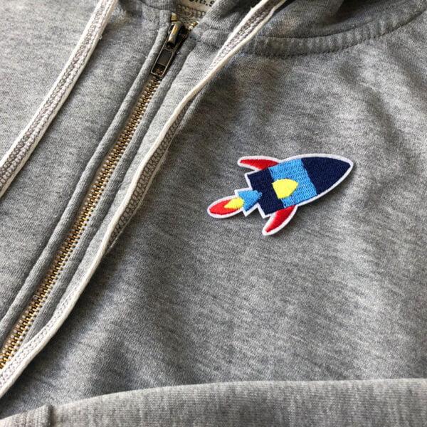 Tygmärke flygande raket på grå töja