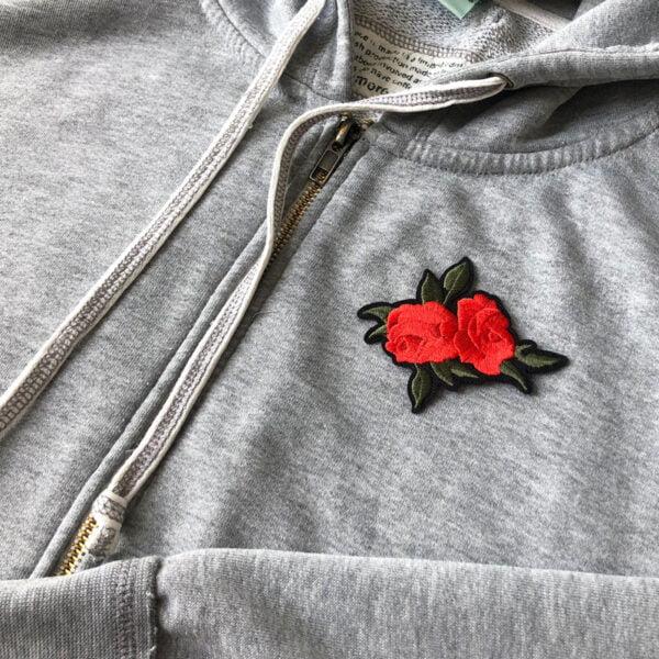 Broderade rosor med gröna blad på grå tröja