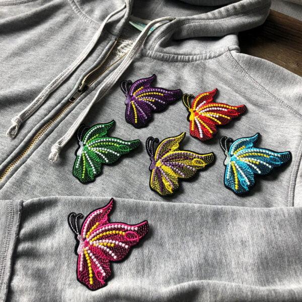 Dekorativa fjärilar på grå tröja - tygmärken