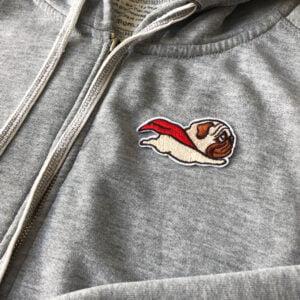 tygmärke på tröja - flygande hund med röd mantel