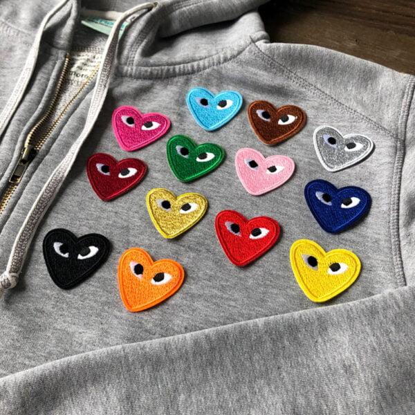 Grå tröja full med tygmärken föreställande hjärtan med ögon