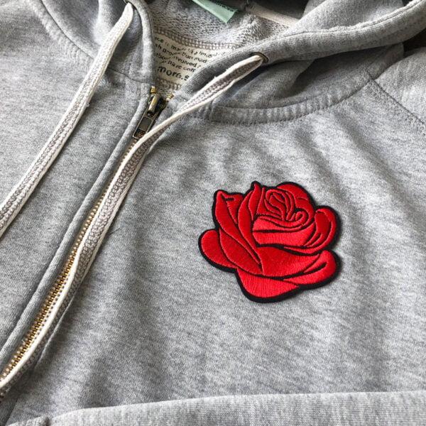 Broderad röd blommande ros på grå tröja