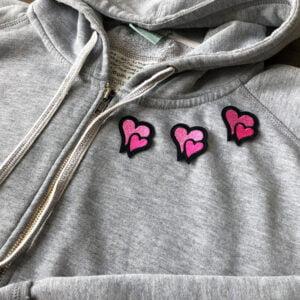 Tre tygmärken i form av små dubbelhjärtan på en tröja