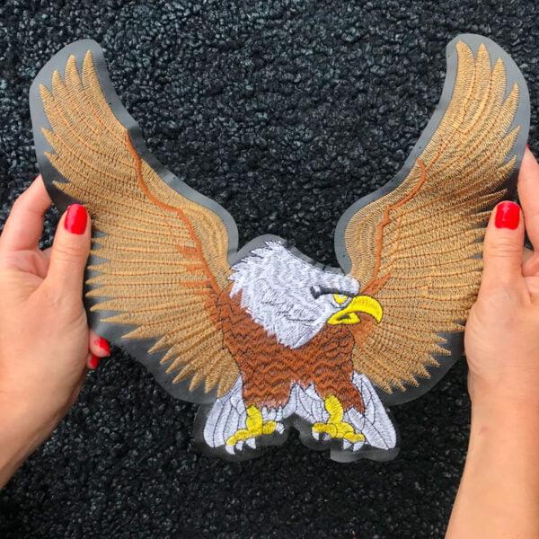Två händer håller upp ett stort tygmärke föreställande en örn med utsträckta vingar