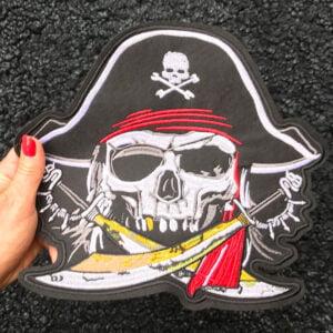 Kvinnas hand håller ett stort tygmärke föreställande pirat med sablar