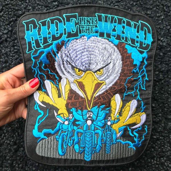 Kvinnas hand håller ett stort tygmärke föreställande Örn MC-tygmärke