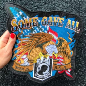 Kvinnas hand håller i ett stort tygmärke föreställande en örn och amerikansk flagga