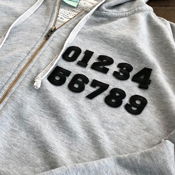 tygmärken svarta siffror på grå tröja
