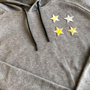Fyra guldfärgade stjärnor på tröja