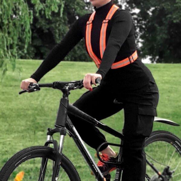 Cyklist som bär en orange reflesele
