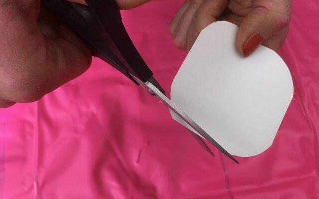 Lagningslapp där hörnen på lappen rundas med sax